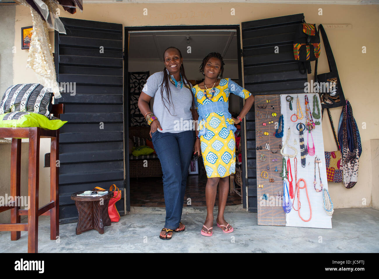 A small shop owner outside her shop, Nigeria, Africa. - Stock Image
