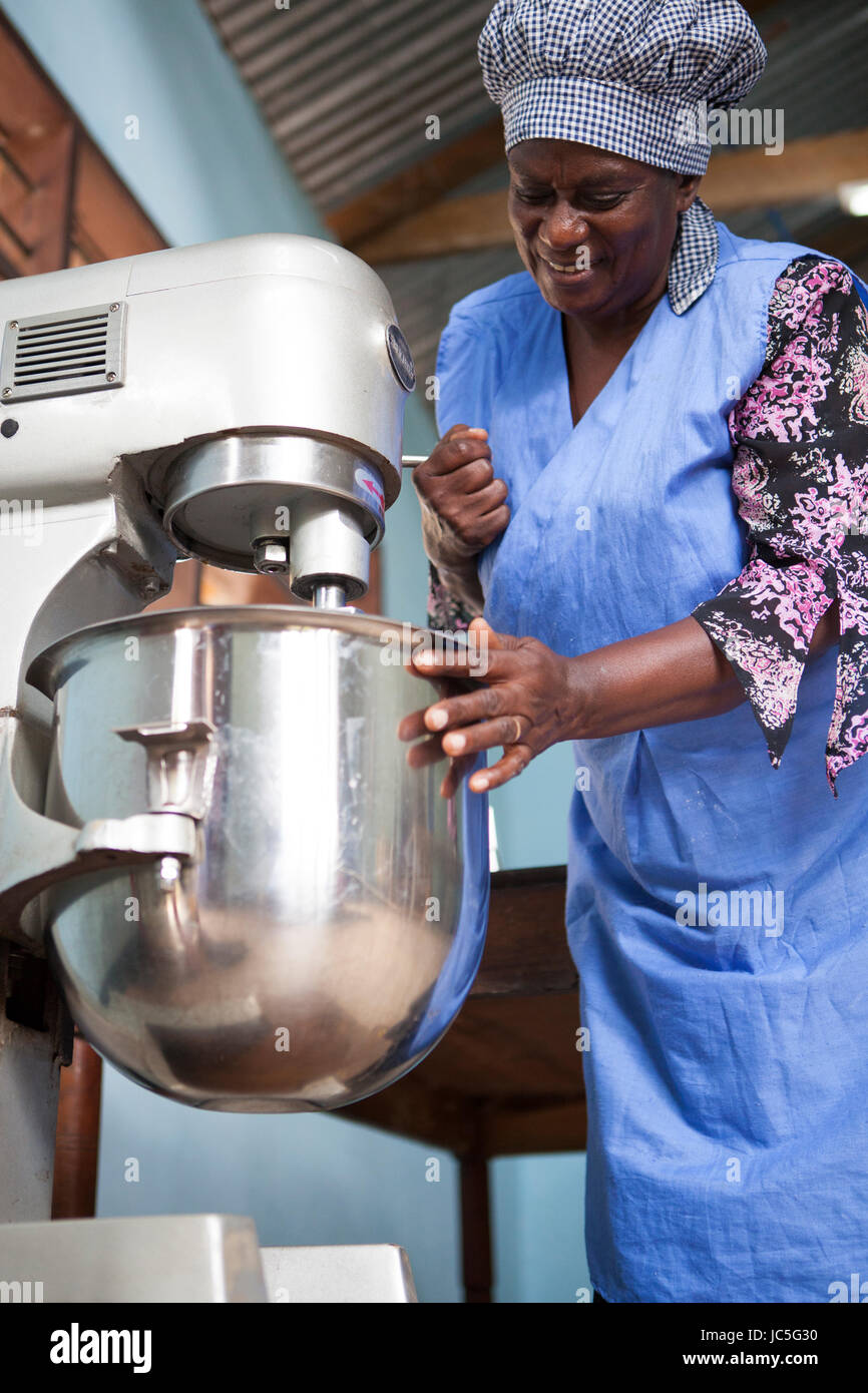 A female baker using her food mixer to make bread. Tanzania, Africa. - Stock Image