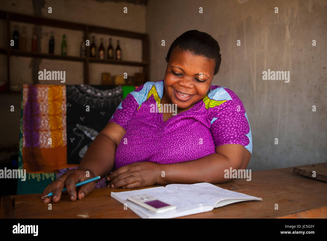 A female small business owner doing some book keeping, Tanzania, Africa Stock Photo
