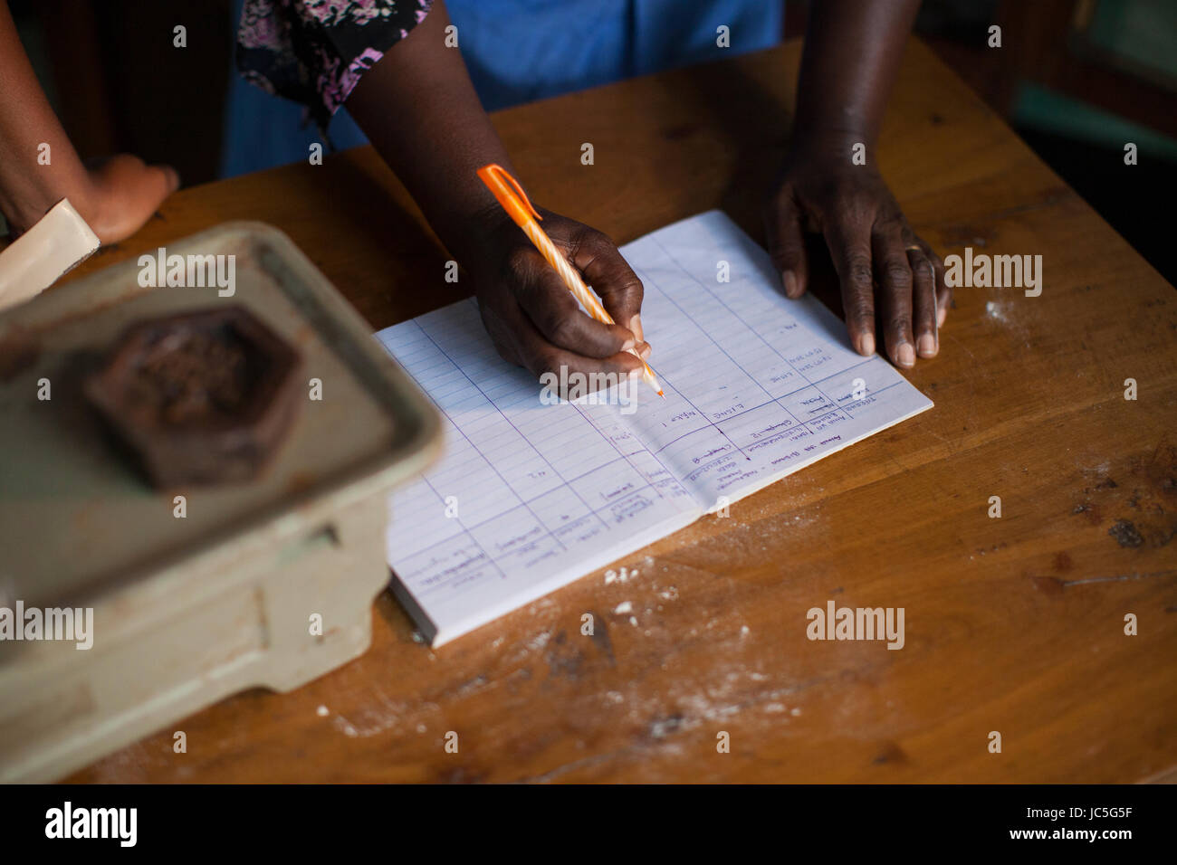 A female small business owner doing some book keeping, Tanzania, Africa. Stock Photo