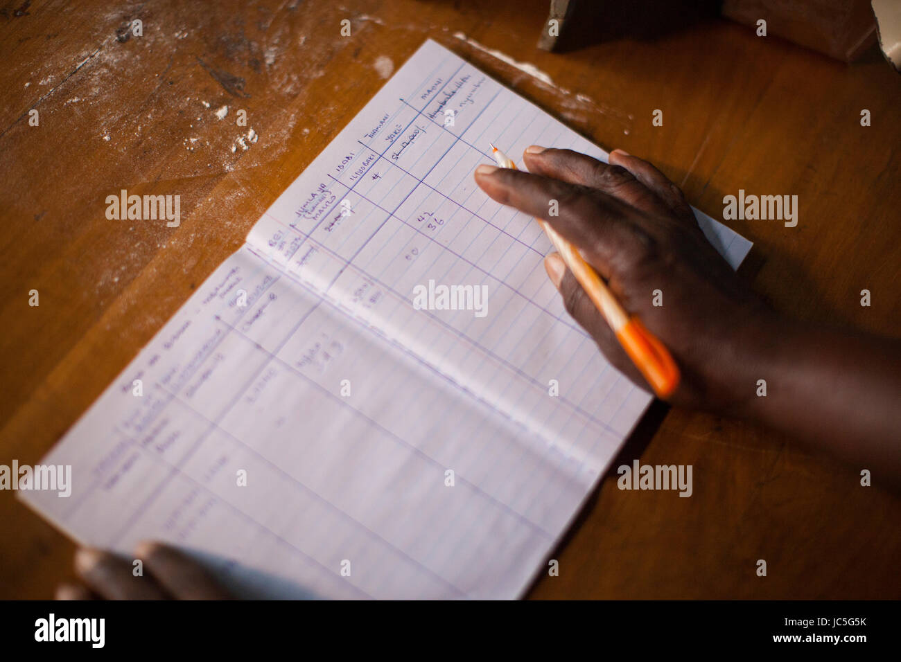 Business woman doing some book keeping, Tanzania, Africa. - Stock Image