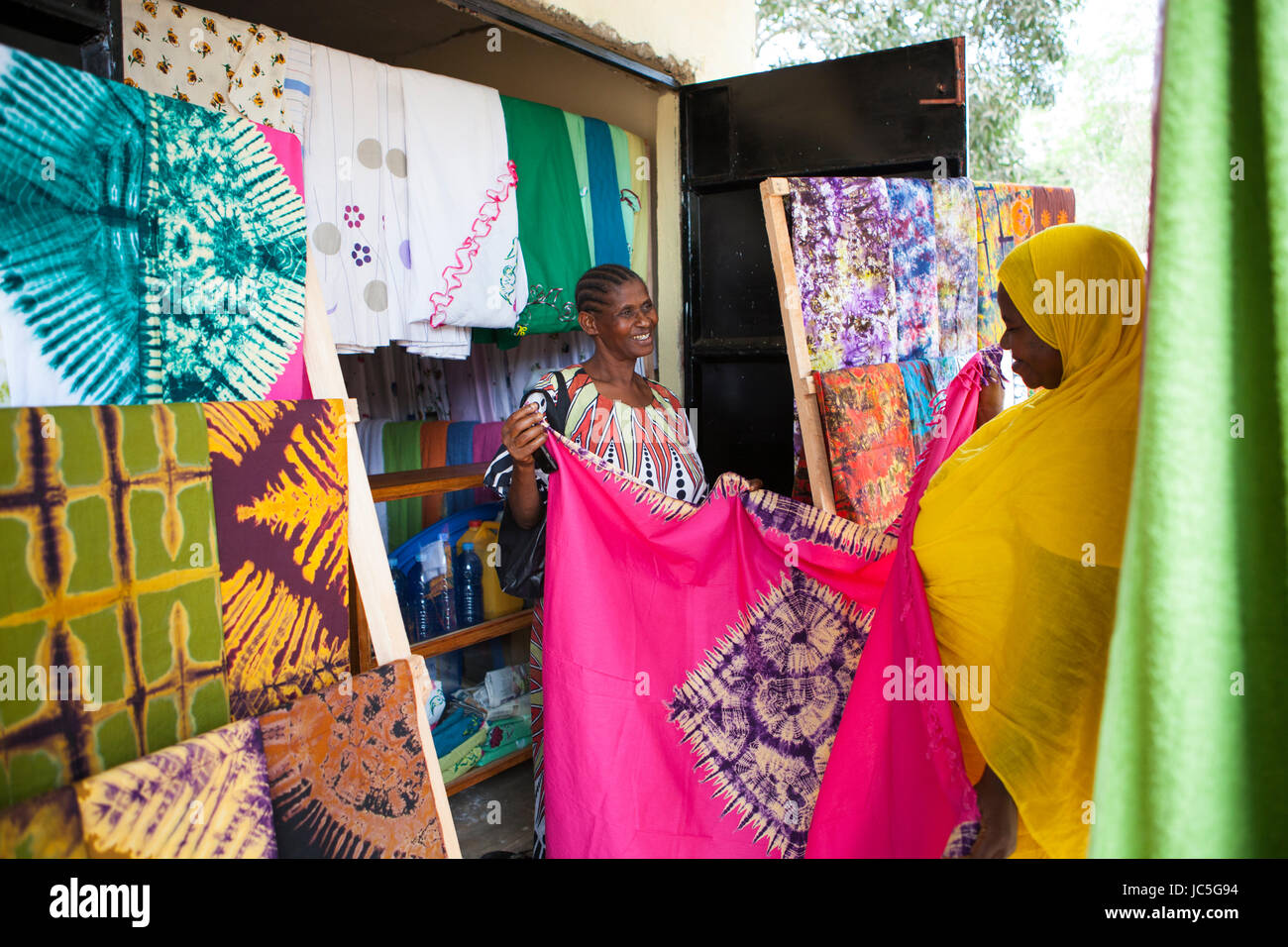 Salma Likupila (right) talking to a customer in her shop A female small business Batik shop owner with a customer, - Stock Image