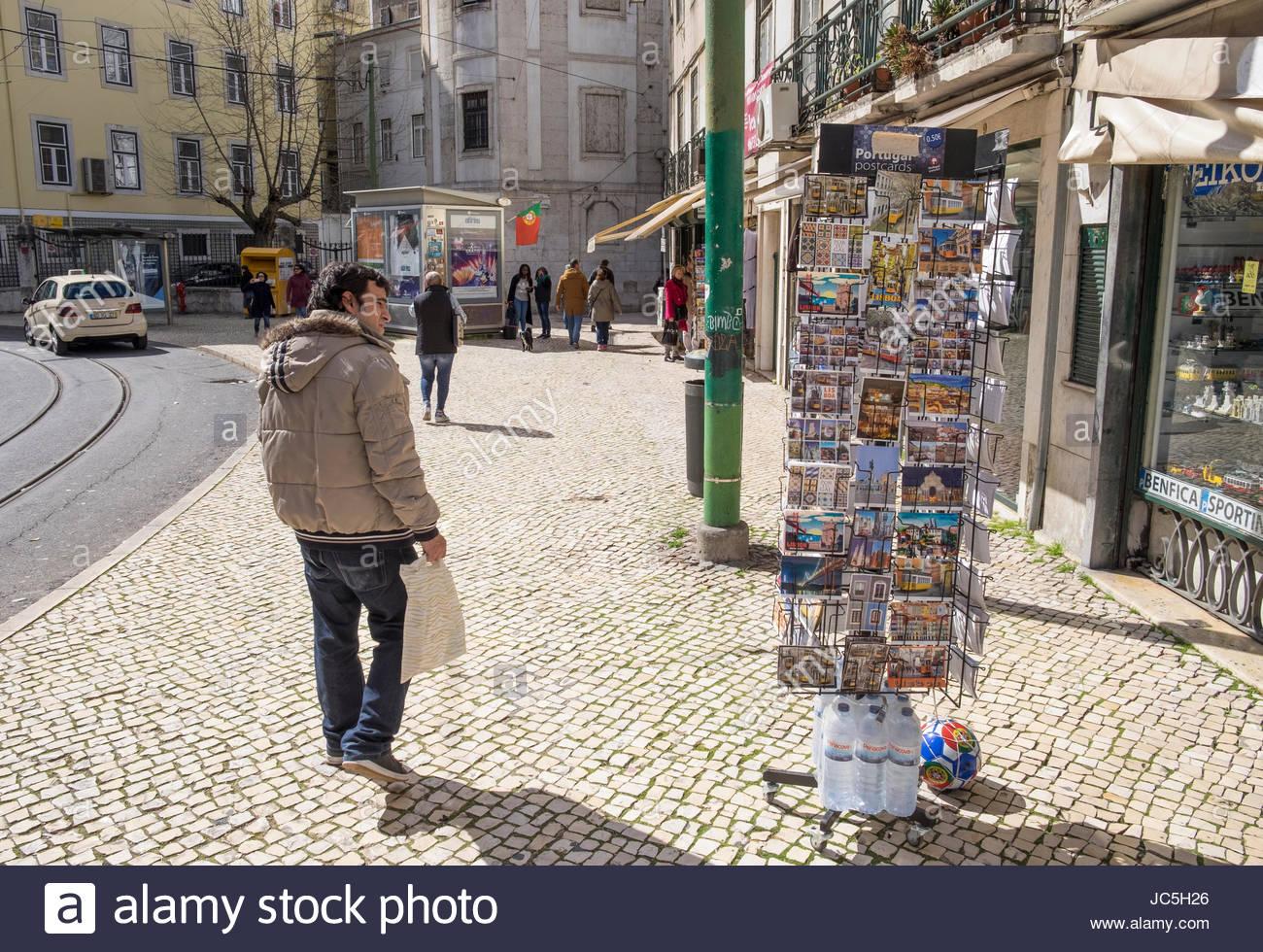 Man walking past postcard rack outside shop along Rua da Palma, Lisbon, Portugal Stock Photo