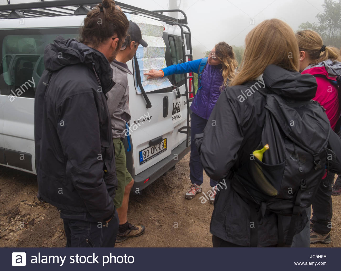 Female guide briefing clients on hiking route of the day using a map on a passenger van, Santuário da - Stock Image