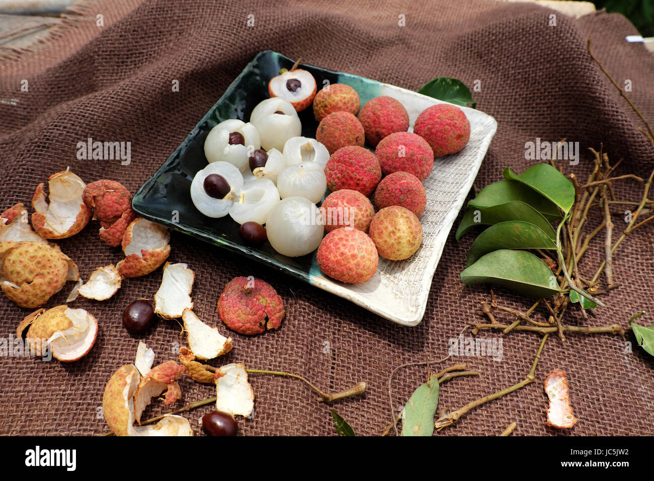Close up plate of fruit on brown background, litchi or lychee fruits or Vai thieu. Red fruit peel with juicy pulp - Stock Image