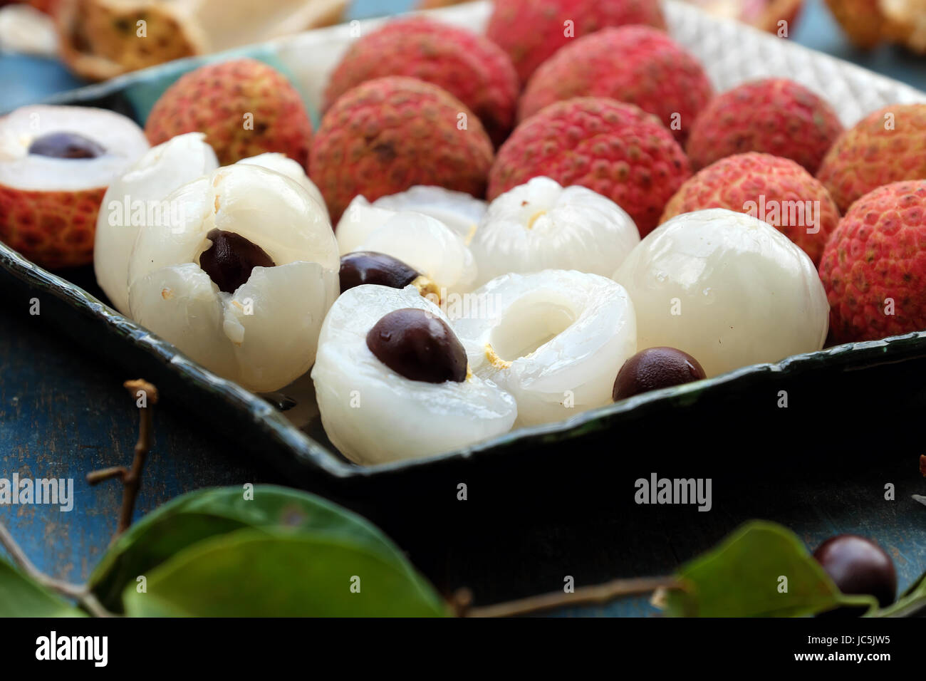 Close up plate of fruit on blue background, litchi or lychee fruits or Vai thieu. Red fruit peel with juicy pulp - Stock Image