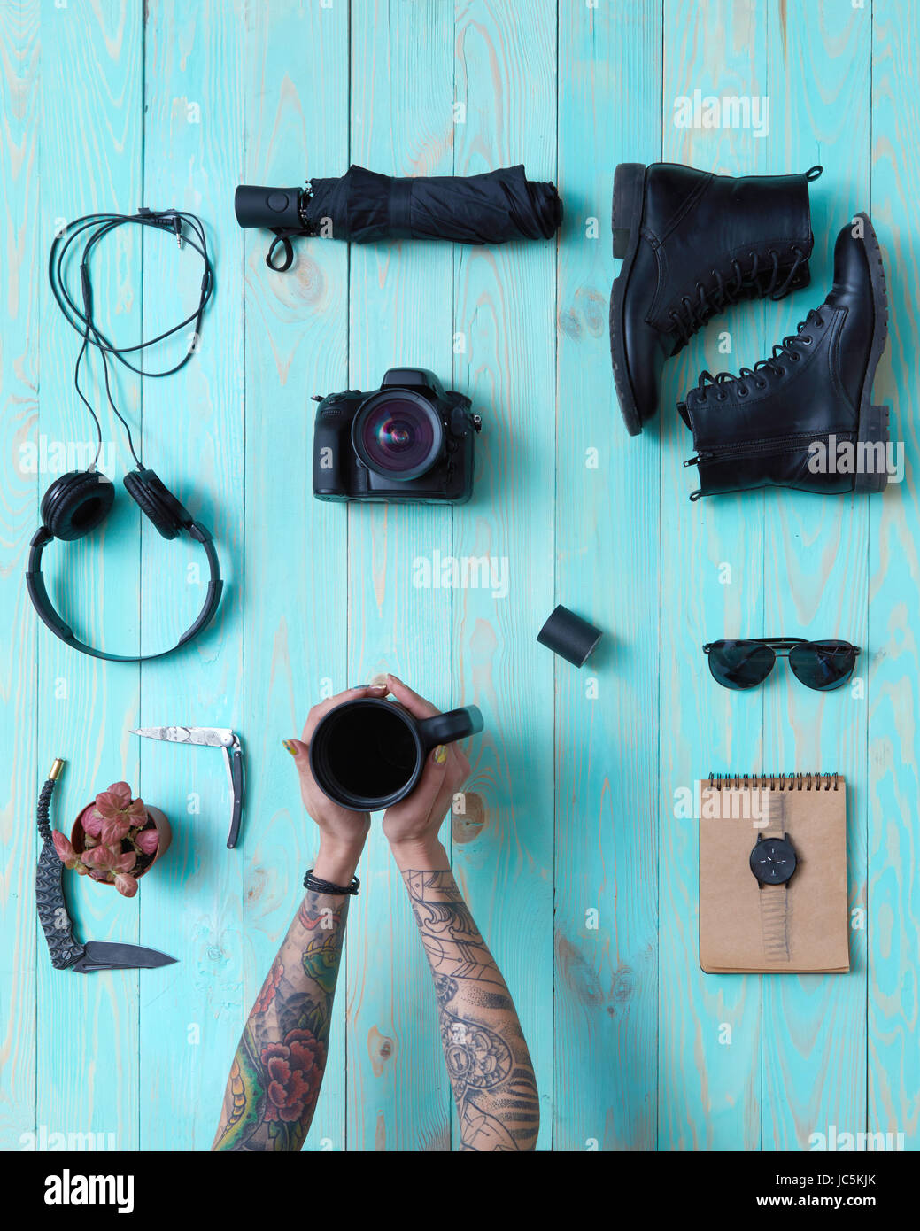 Set of cool things for travel on a blue wooden background With female hands with tattoos holding a cup of coffee - Stock Image