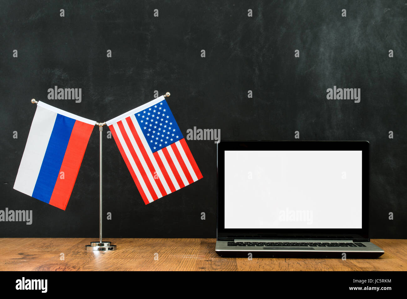 Russia spying on America. Russian hackers threaten USA computer networks political problem flag on flagpole in front Stock Photo