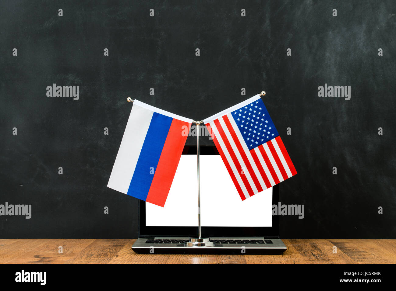 Concept of hacking into the computer of American and Russian political problem flag on flagpole in front of black Stock Photo