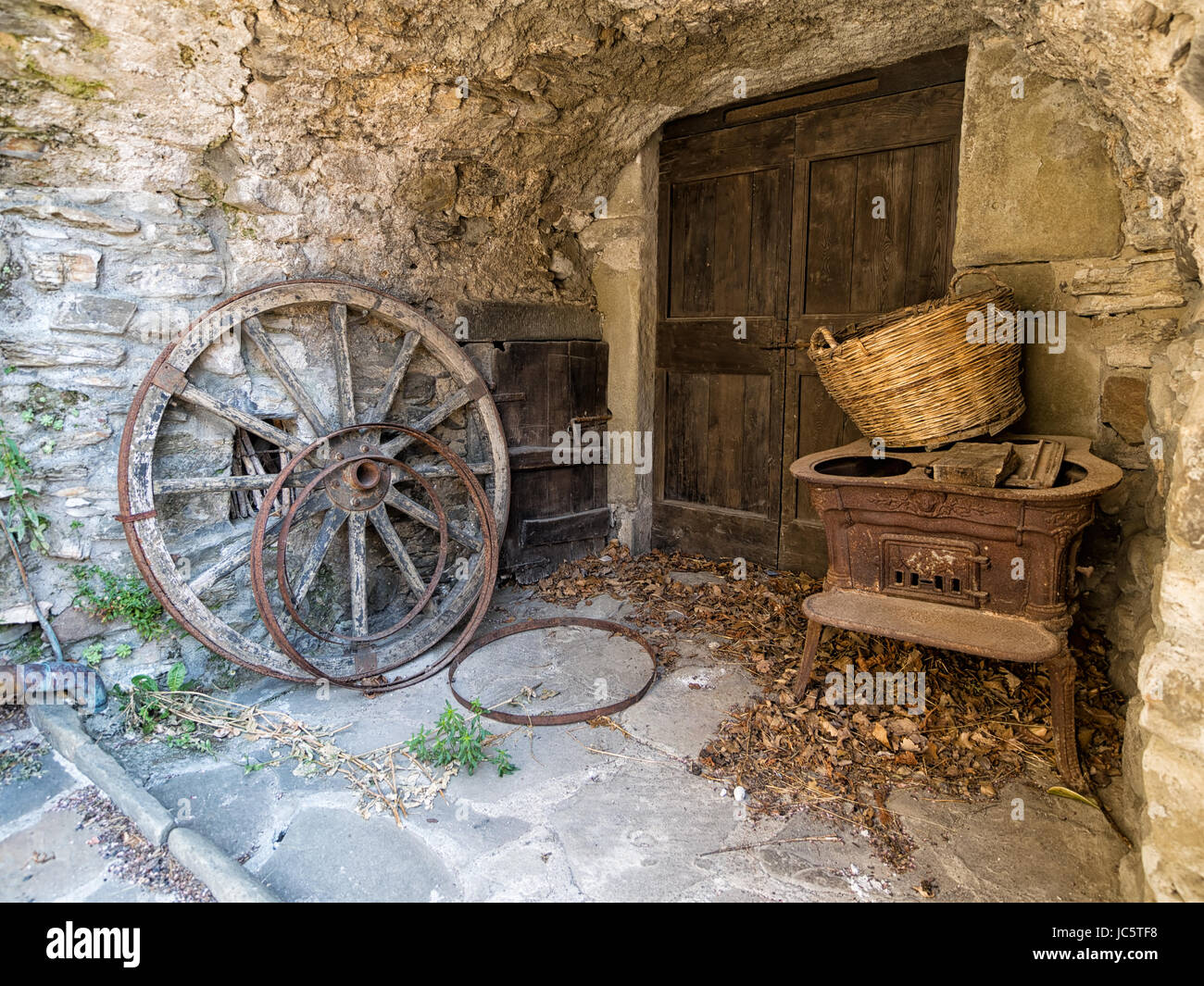 Rustic rural remains with crtwheels and old stove. Italian village. - Stock Image