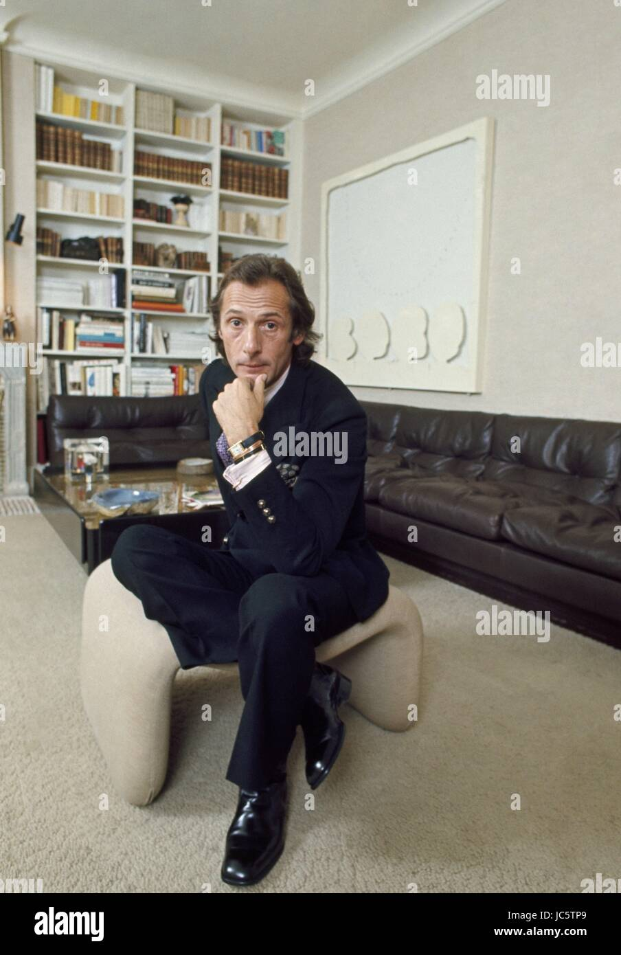 French fashion designer Marc Bohan posing in his Paris appartment, c.1972. Above the sofa, a painting by Montana. - Stock Image