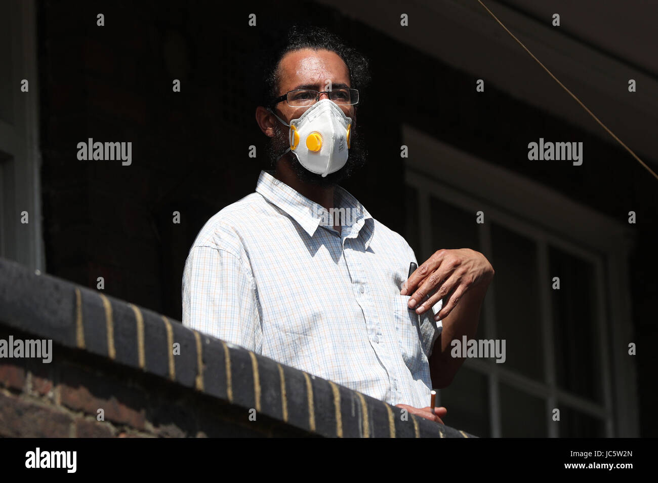 A man wearing a face mask looks on from Bramley House, a building close to the scene of a fire that has engulfed - Stock Image