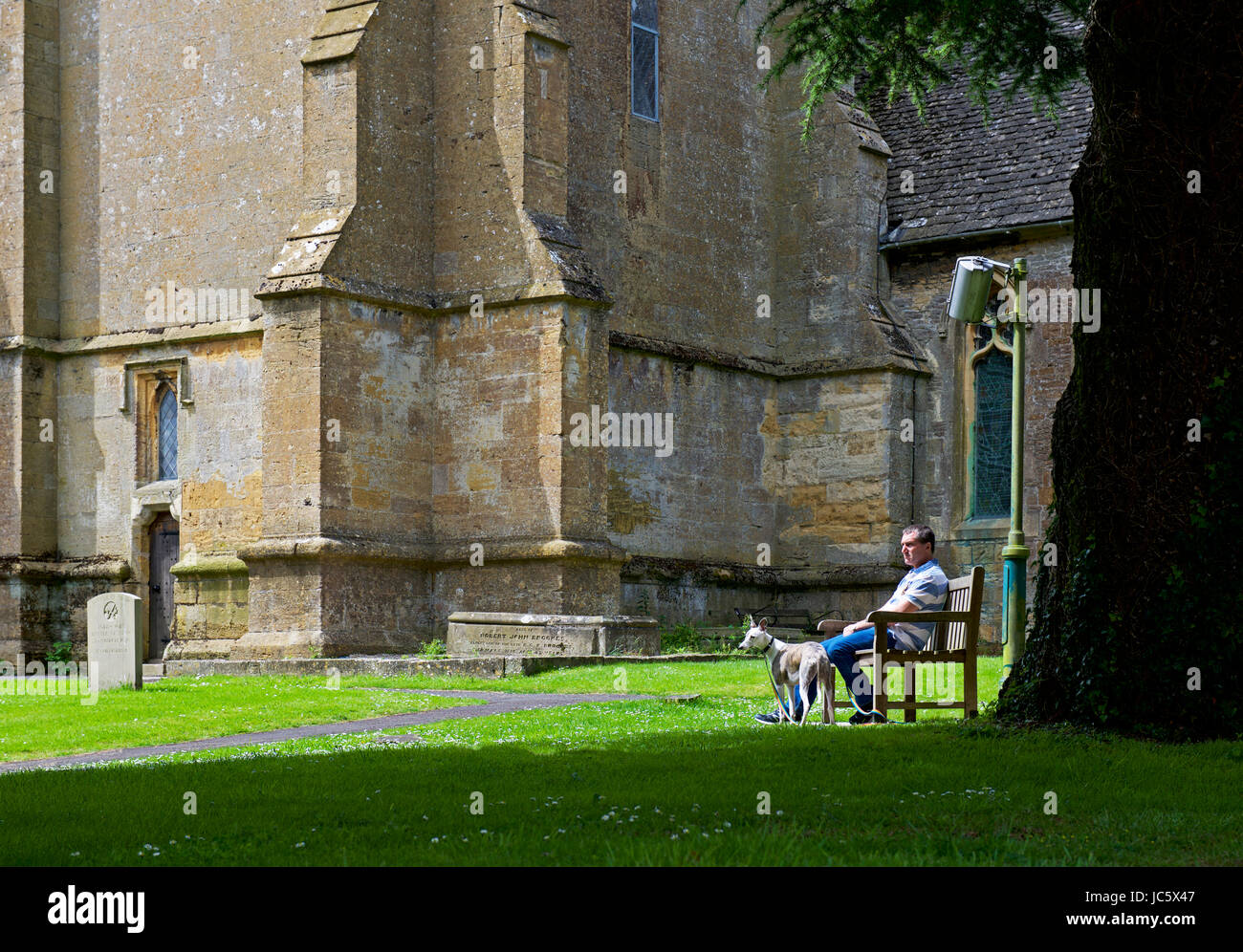 Man and dog and St Edward's's Church, Stow on the Wold, Gloucestershire, England UK Stock Photo