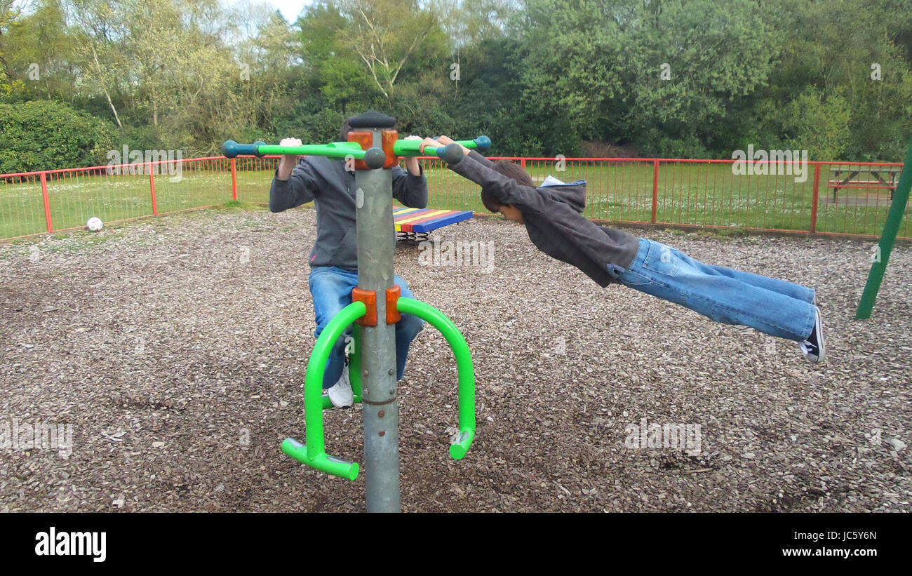 Young boy spinning on playground spinner and swinging out horizontally while hanging on with his hands - Stock Image