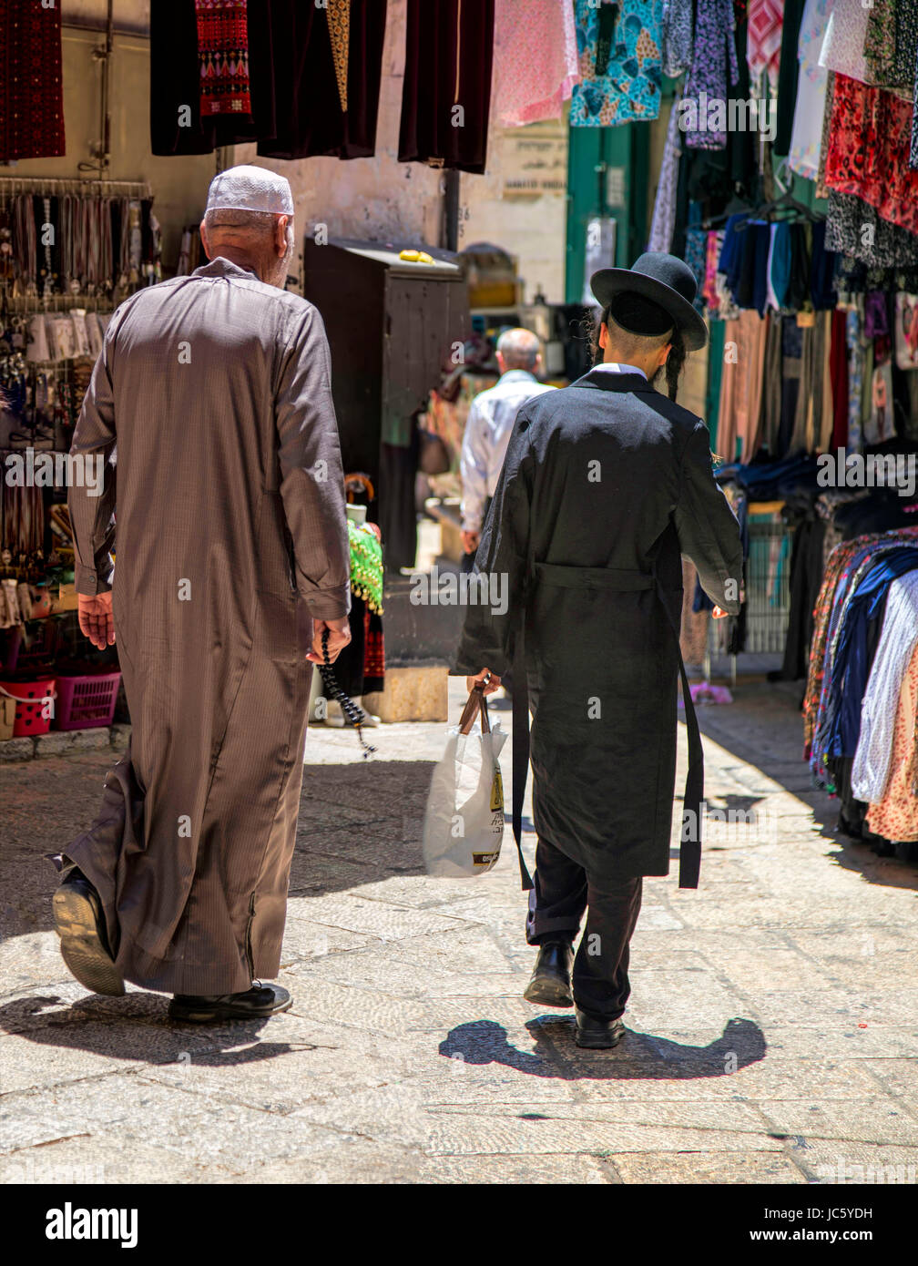 Street view of an old Arab man with prayer beads and a young Orthodox Jew lwith sidelocks carrying his shopping, - Stock Image
