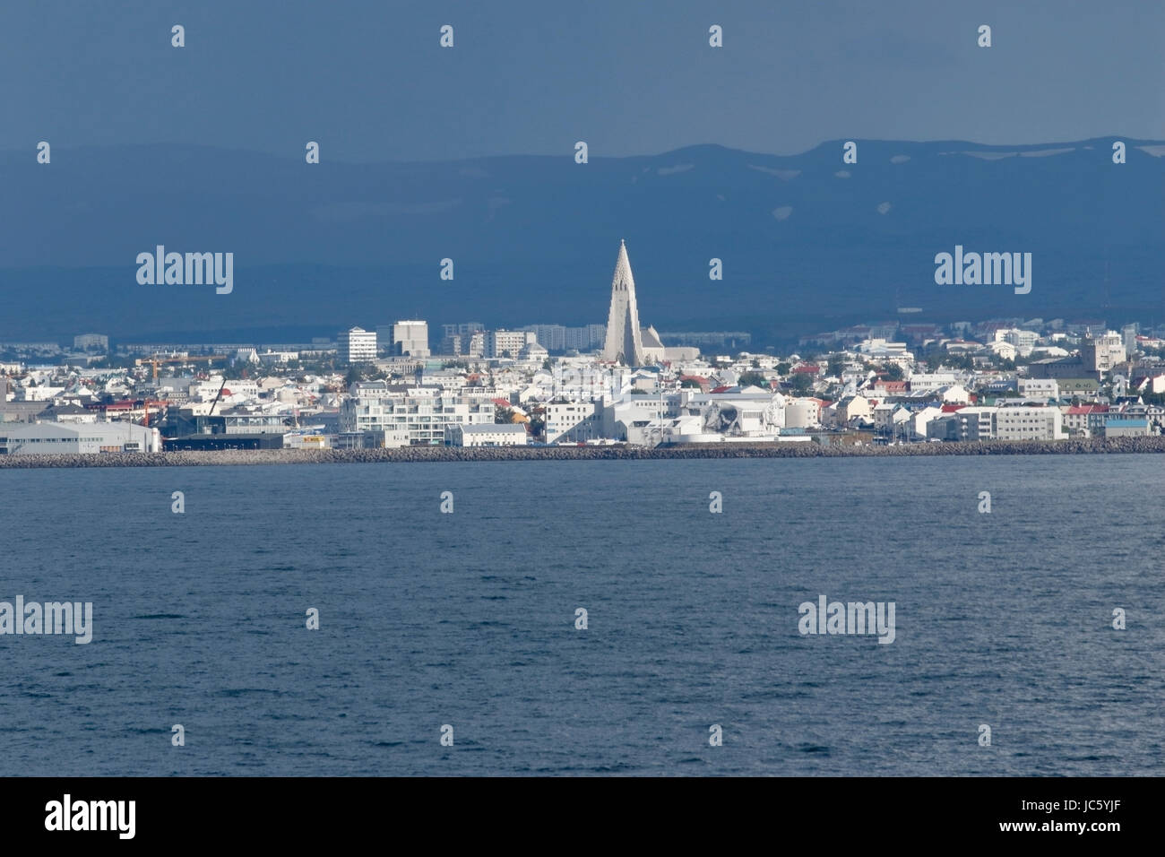 view of Reykjavik city, Iceland, from the sea, showing the cathedral in the distance - Stock Image