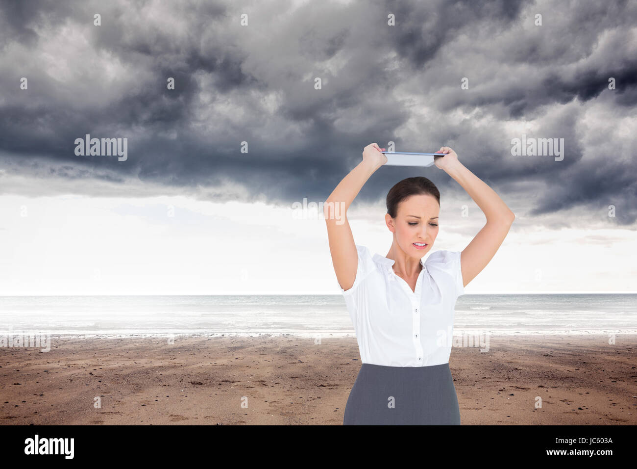 Composite image of angry businesswoman throwing her tablet pc while posing - Stock Image