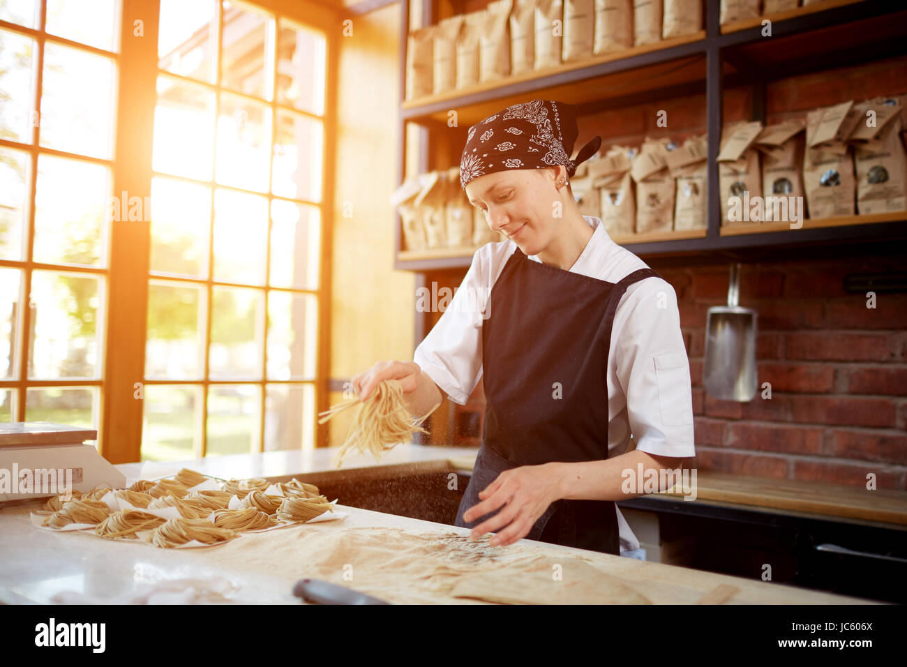 Woman cooking noodles in cafe - Stock Image