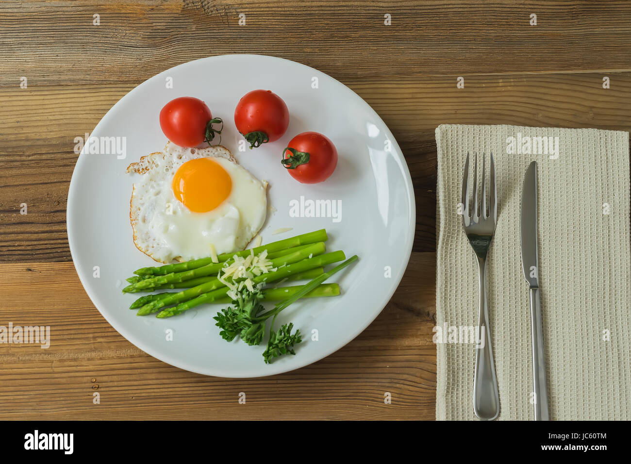 Green asparagus with fried egg, cherry tomatoes for healthy breakfast. - Stock Image