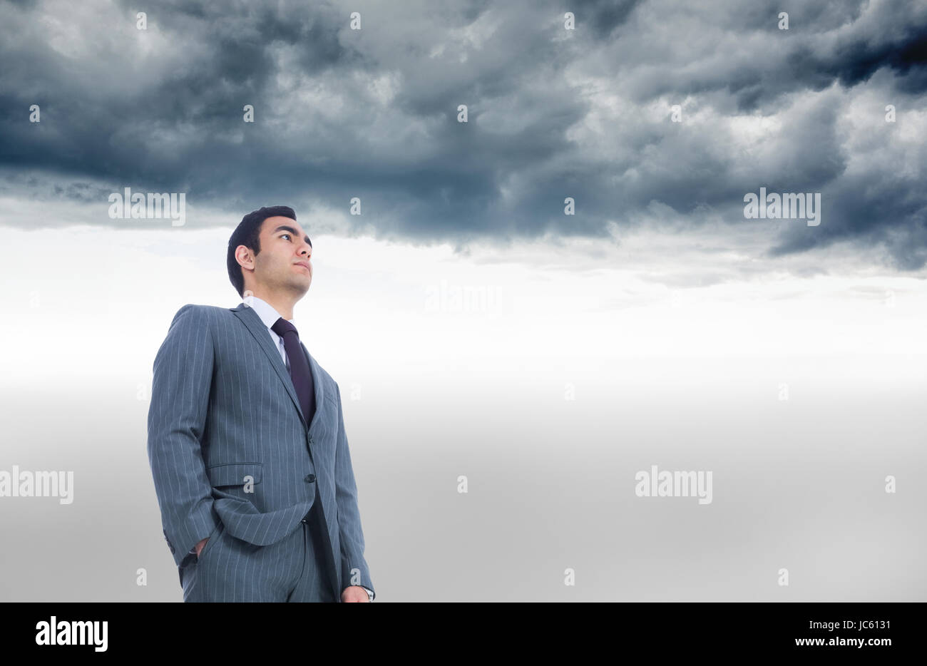 Composite image of unsmiling businessman standing - Stock Image