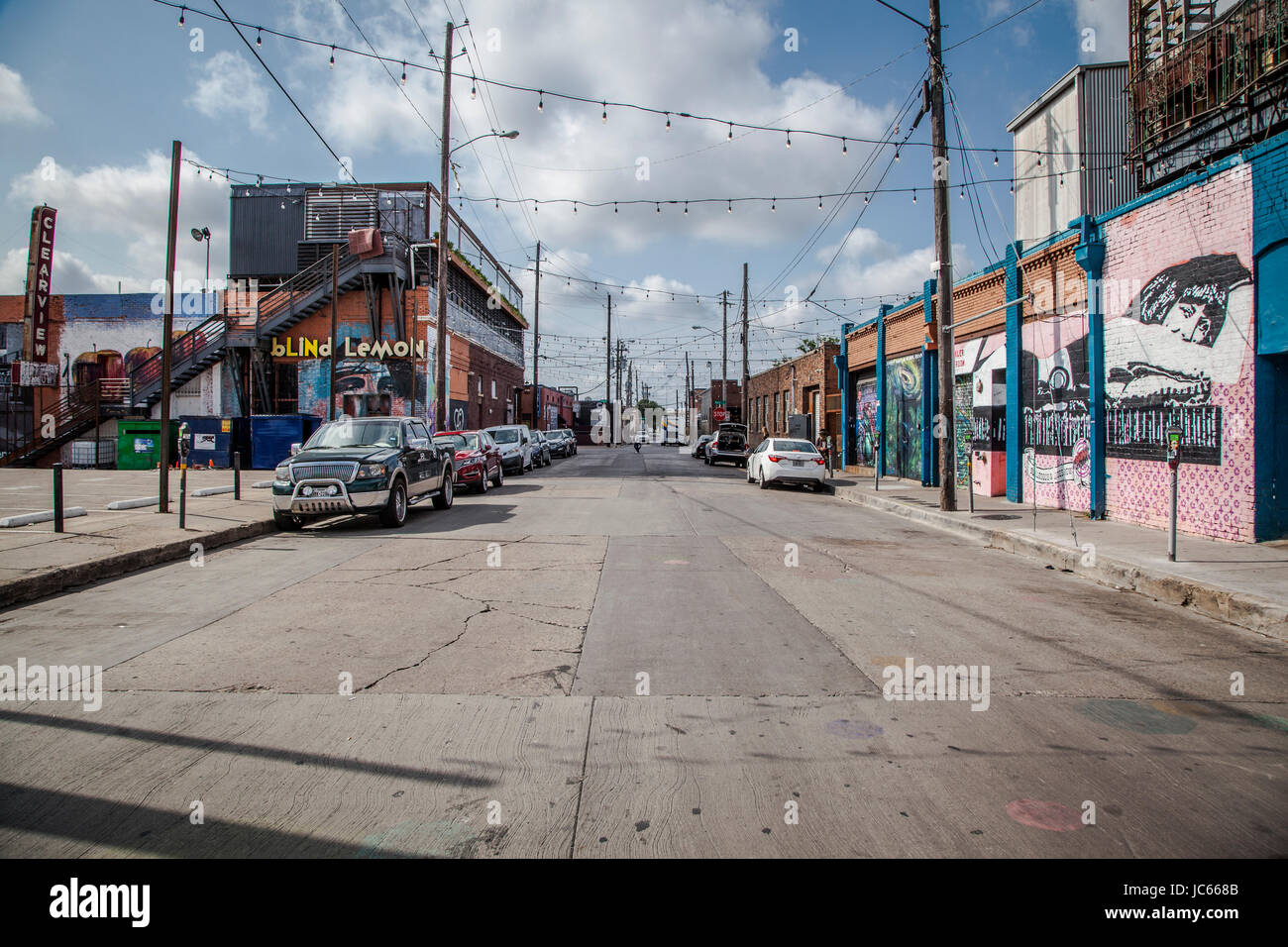 Paintings on wall along a sidewalk in Dallas Deep Ellum. - Stock Image