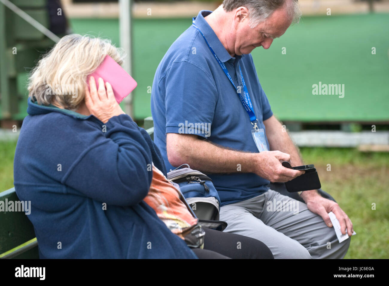 Senior man & woman on smartphones at Hay Festival of Literature and the Arts 2017 Hay-on-Wye Powys Wales UK Stock Photo