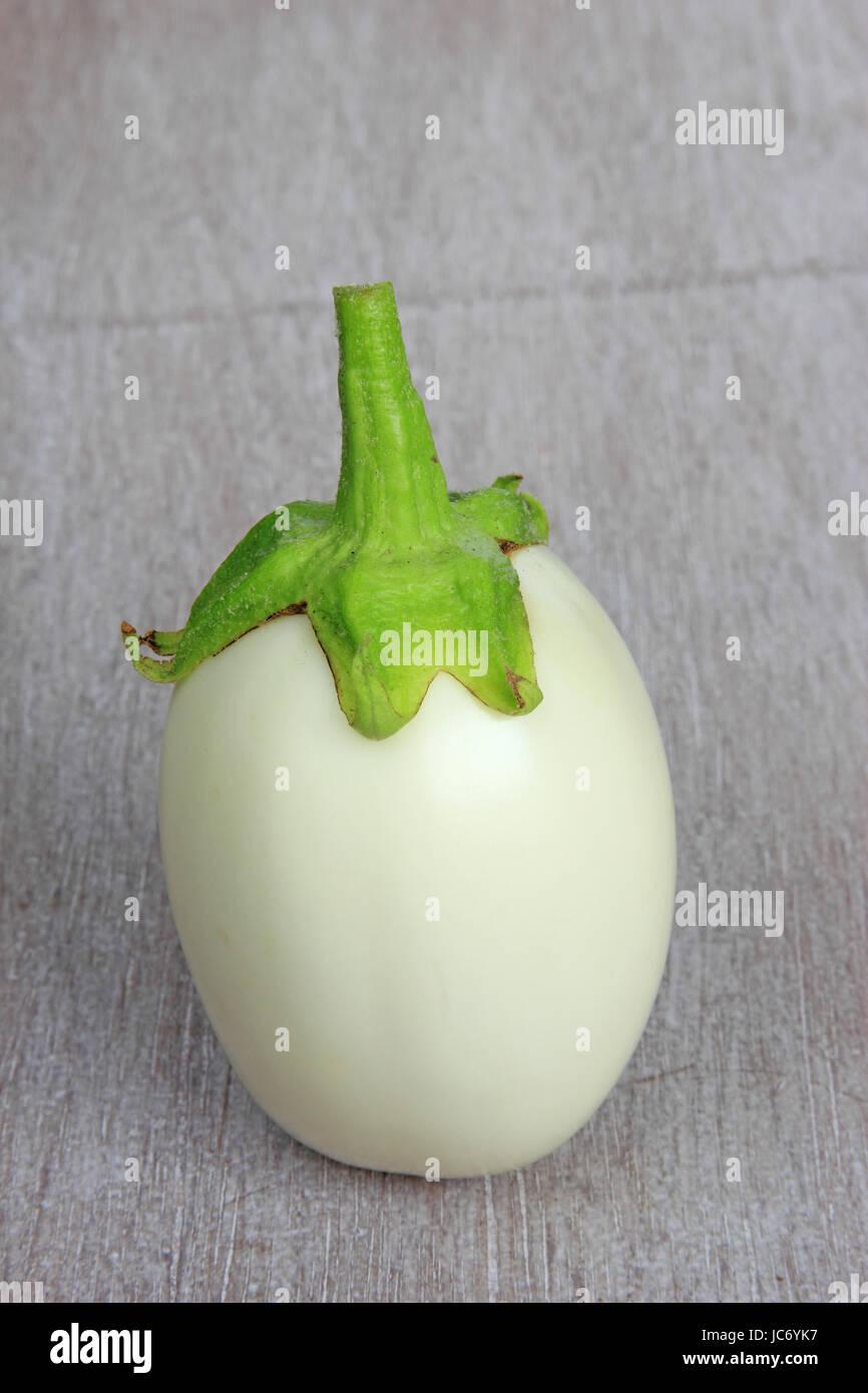 Weiße Aubergine (Solanum melongena) liegt auf rustikalem Holzbrett Stock Photo