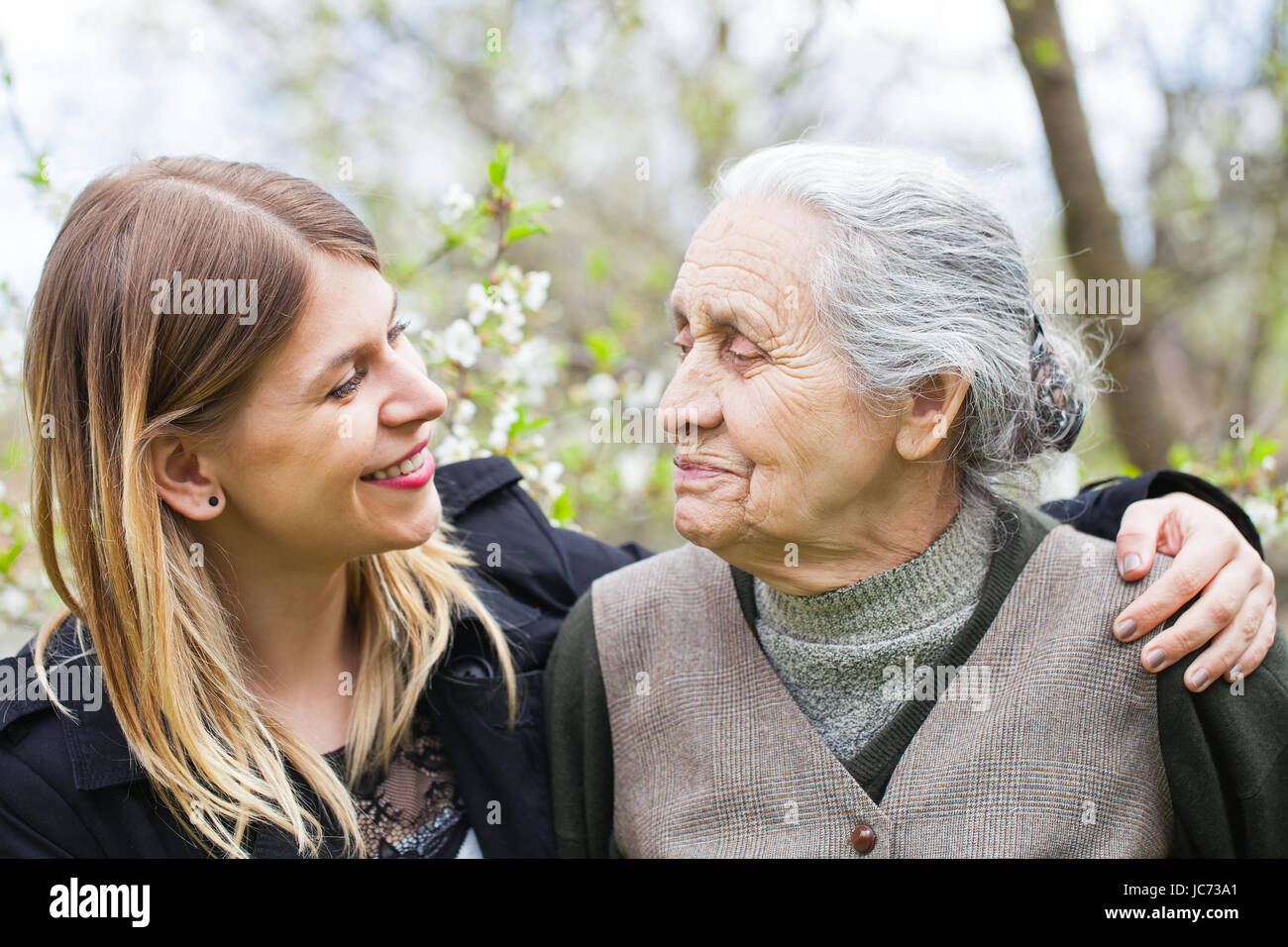 Picture of a happy elderly woman with her cheerful carer outdoor springtime - Stock Image