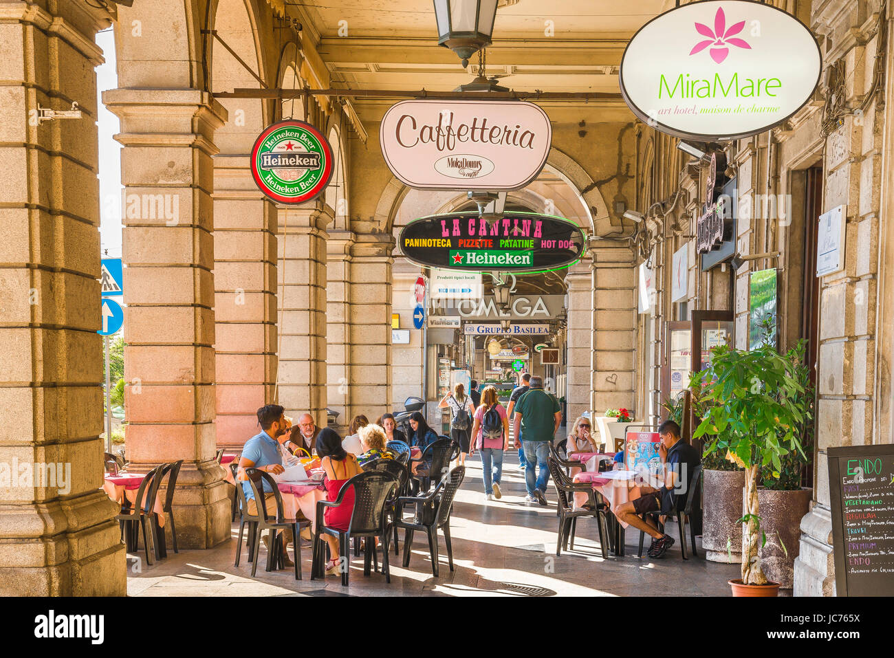 Cagliari arcade, people relax at a cafe terrace inside an arcaded street in the Via Roma in the Marina quarter of - Stock Image