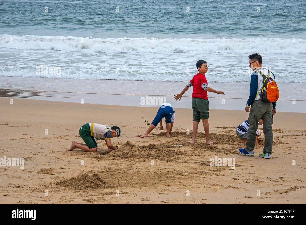Children Playing on Sandy Beach, Hong Kong - Stock Image