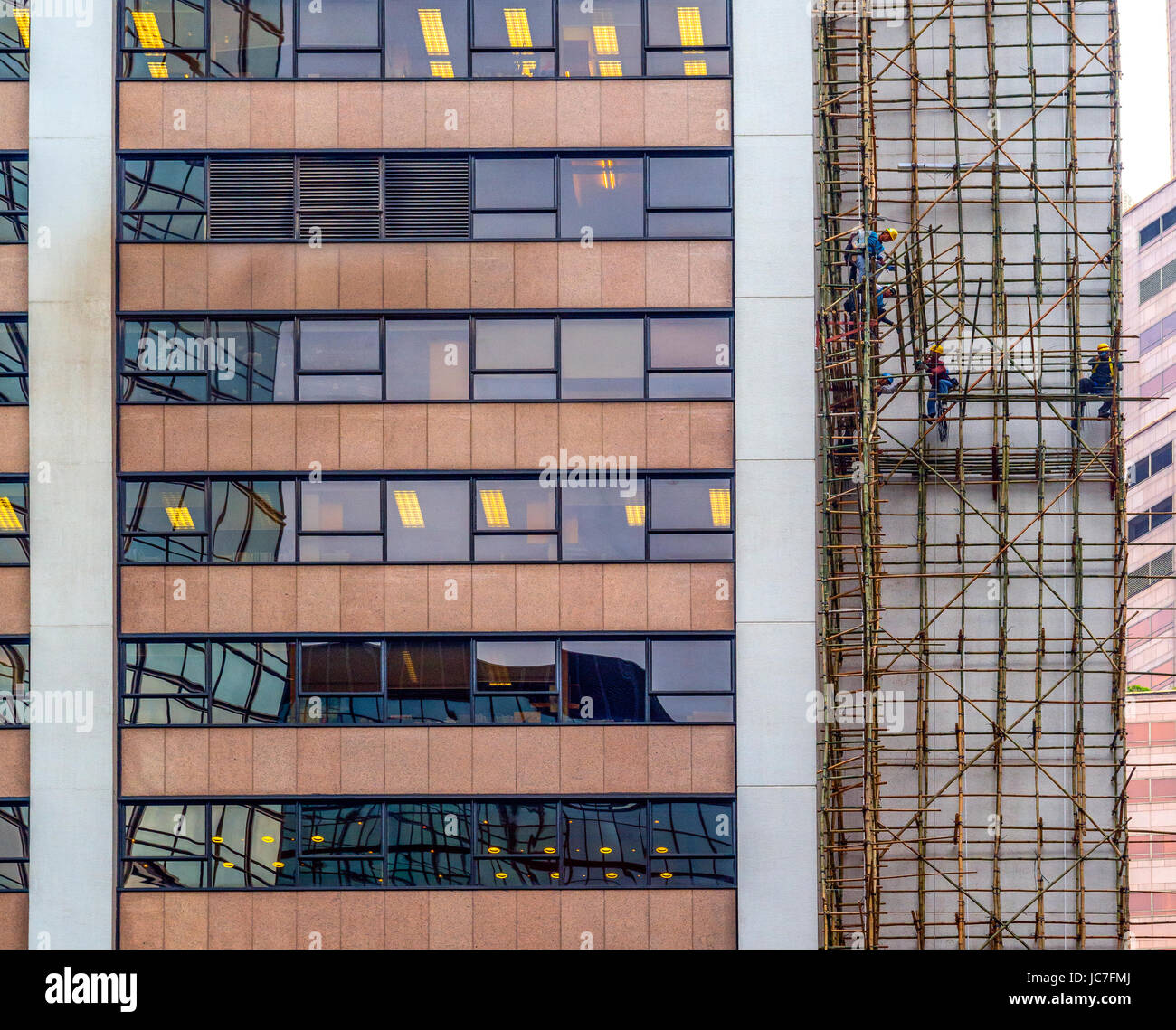 Bamboo Scaffolding and Workmen on high-rise building, Central, Hong Kong - Stock Image