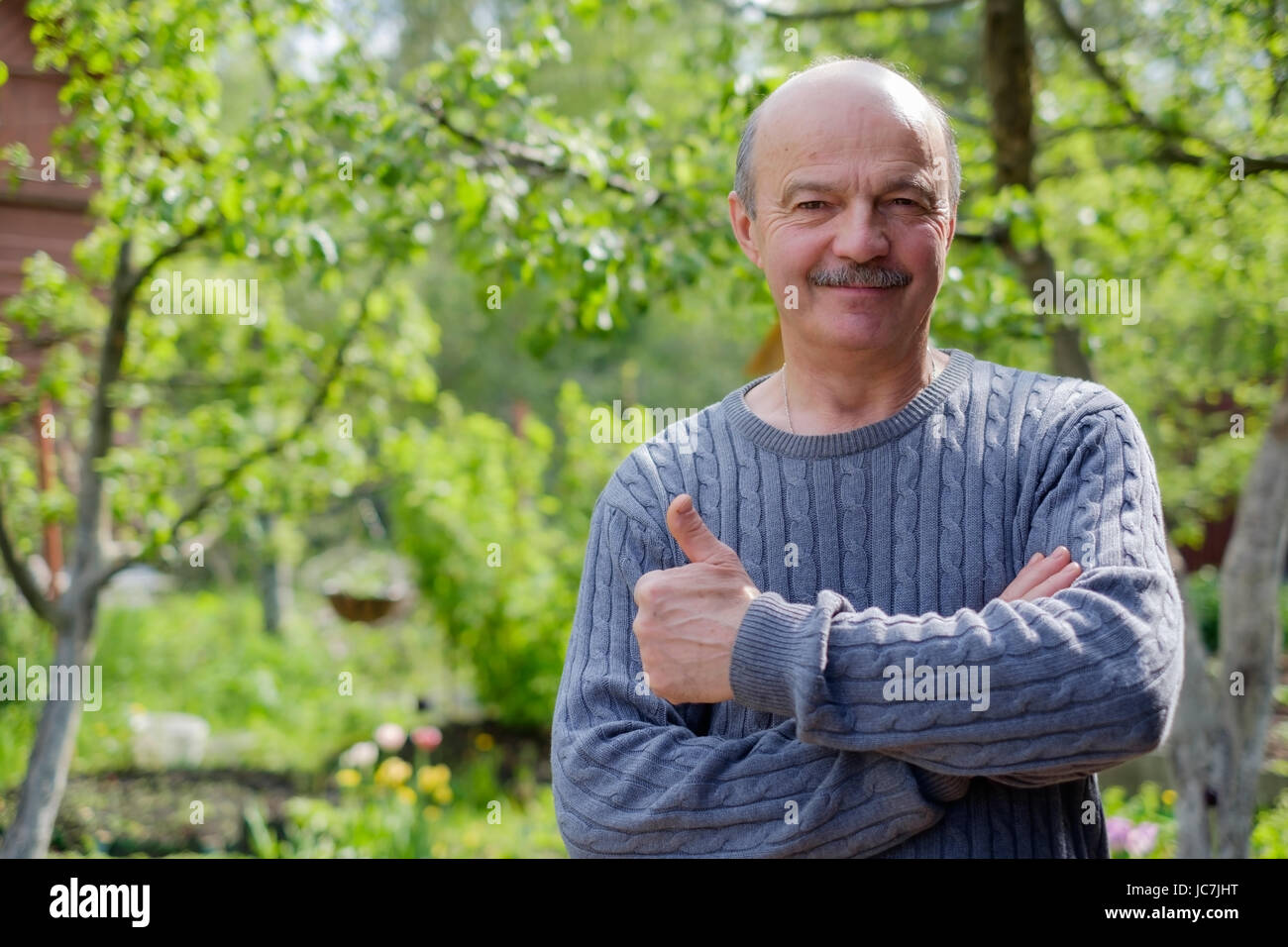 Mature man sitting in garden near apple tree in countryside. He shows thump up. - Stock Image
