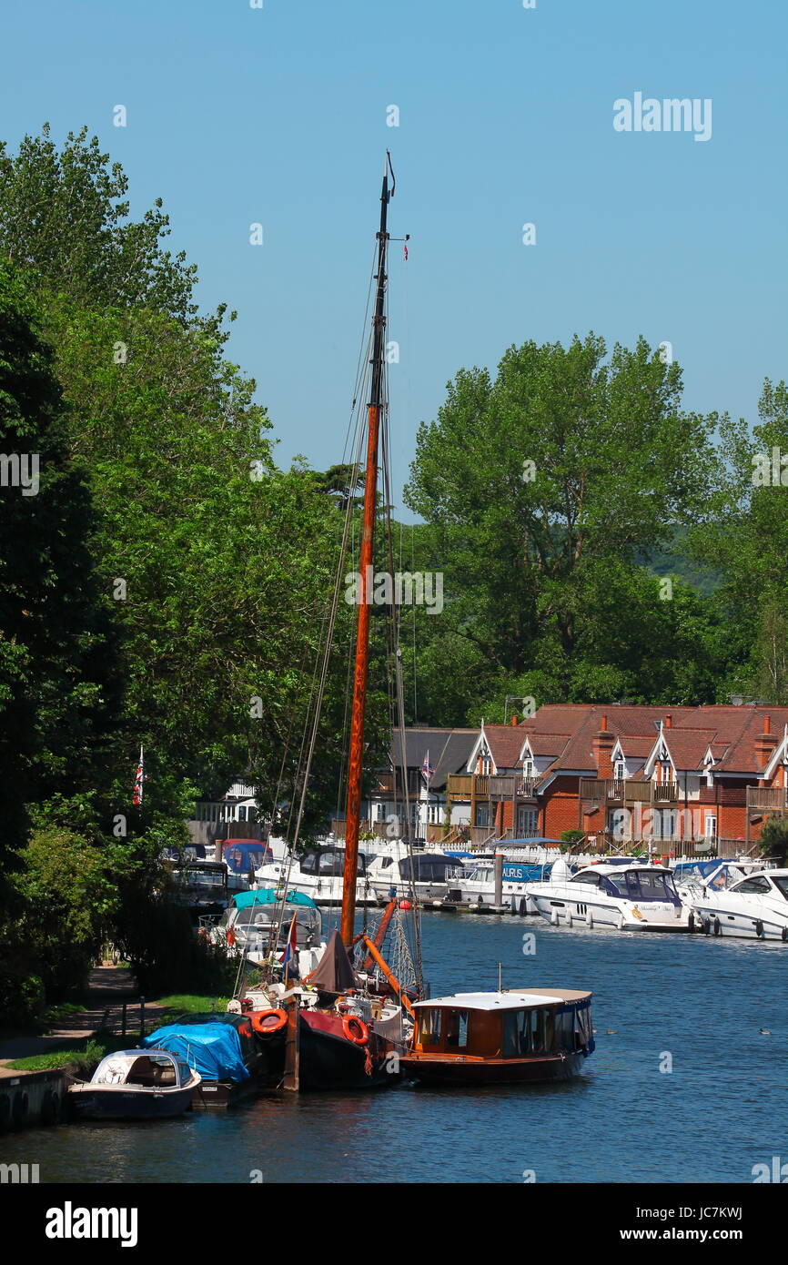 Looking out towards the Bourne end Marina with its riverside mooring for and houses with huge trees behind. - Stock Image
