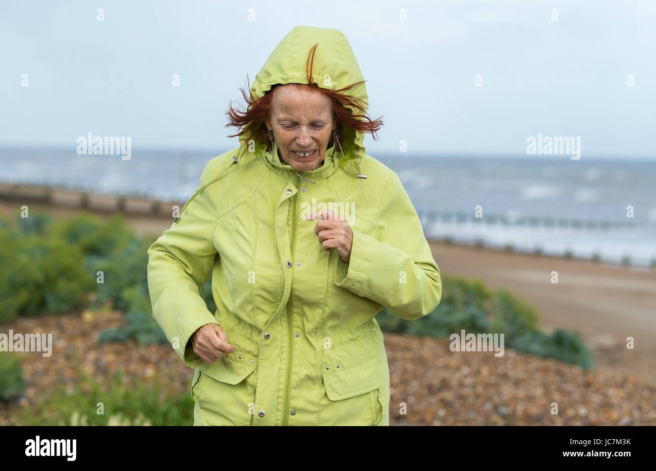 Middle aged woman running on a beach in cold weather dressed in a coat to keep warm, on a dull day in the UK. - Stock Image