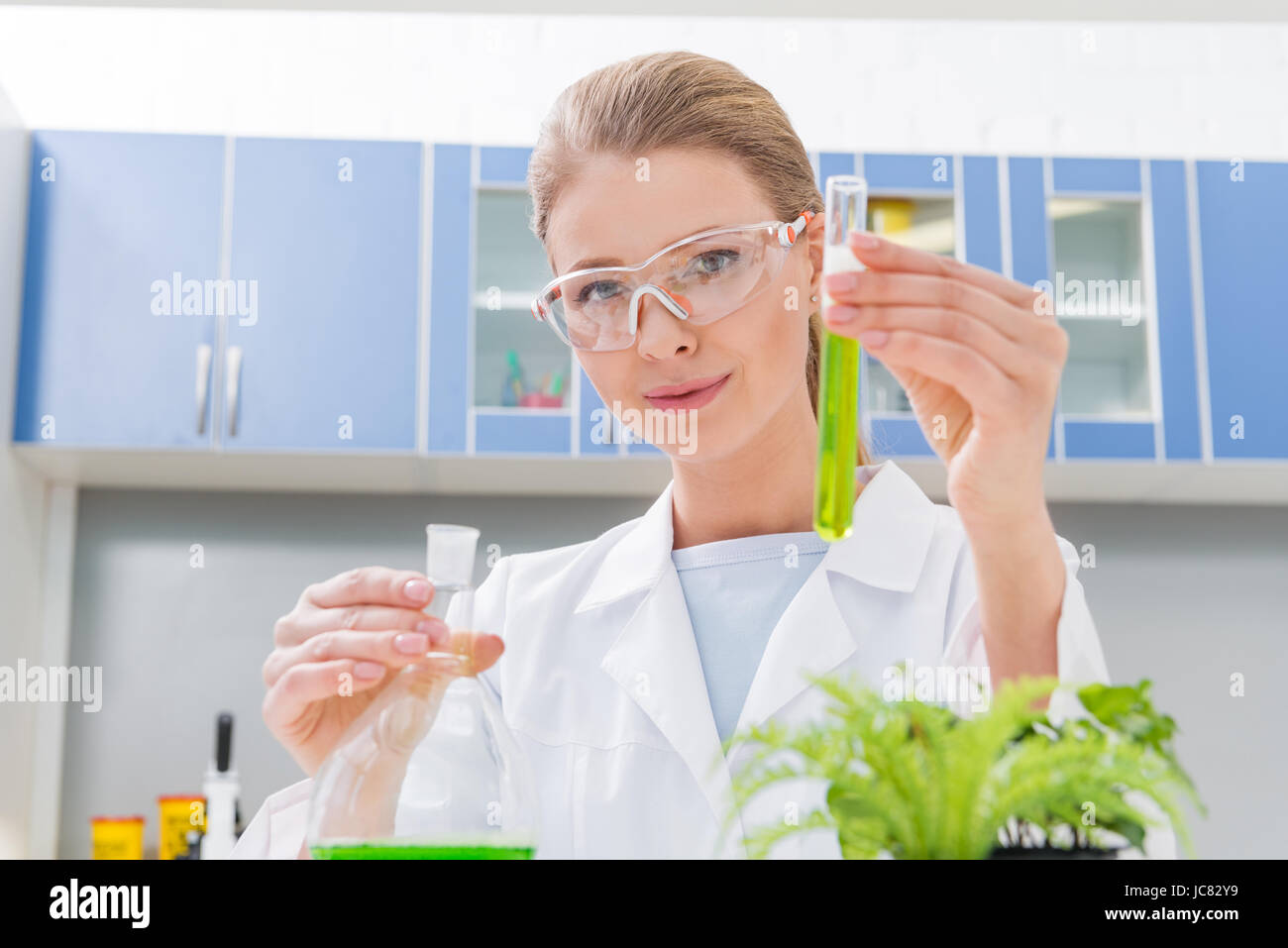 scientist holding tubes with reagents in laboratory looking at camera - Stock Image