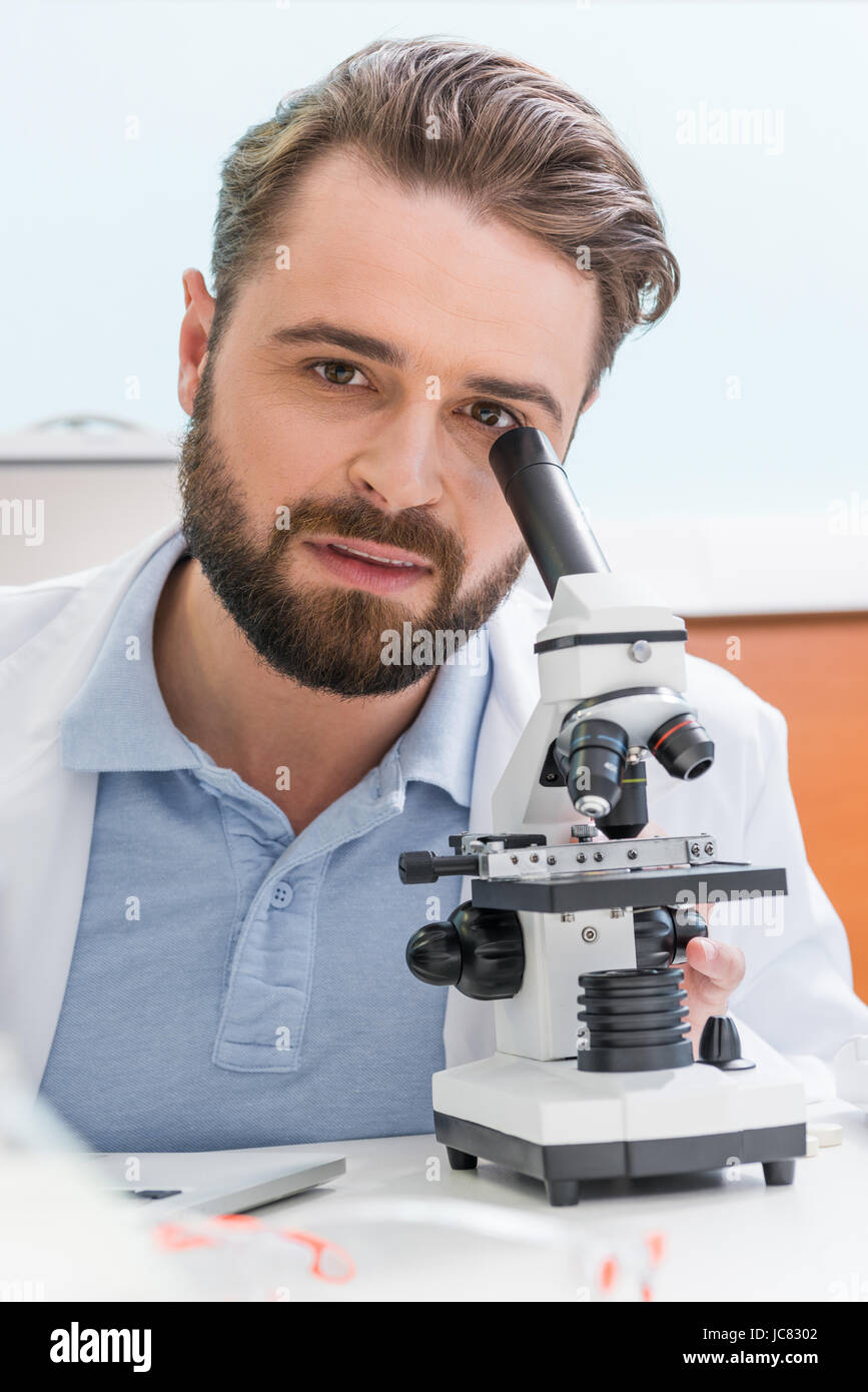 bearded scientist working with microscope and looking at camera in laboratory - Stock Image
