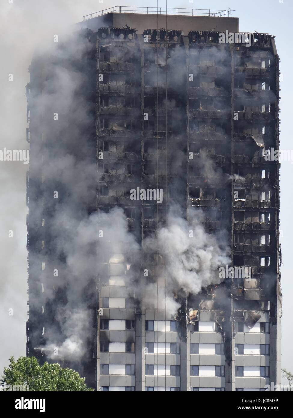 Firefighters are trying to stop he fire in West London where the Grenfell Tower was blazing over night, meanwhile - Stock Image