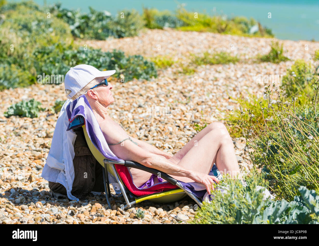 Elderly woman relaxing in a chair on a shingle beach on a hot Summer's day in June 2017 on the south coast of - Stock Image