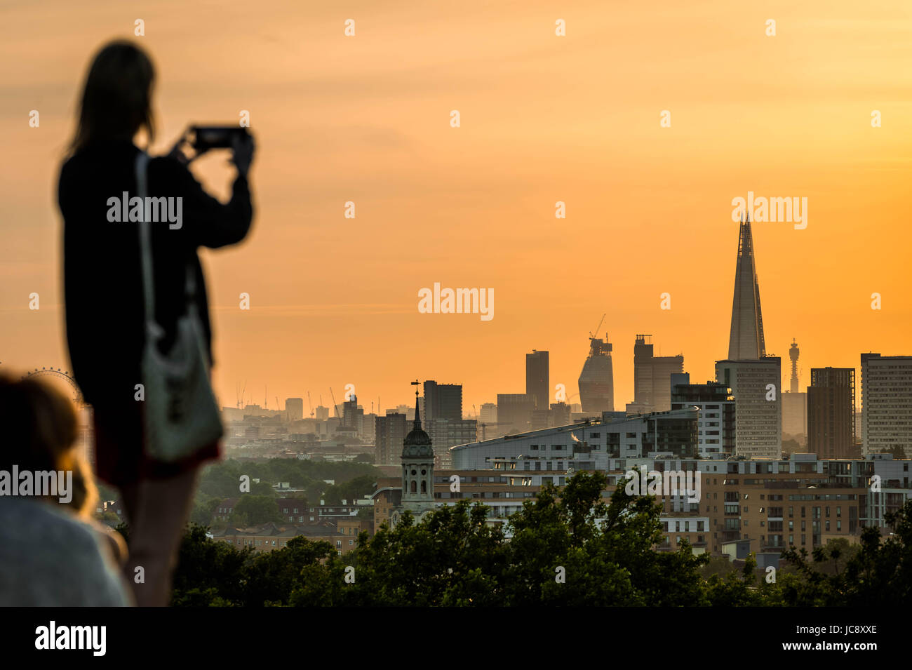 London, UK. 14th June, 2017. UK Weather: Locals and tourists enjoy the evening sunset over the city seen from Greenwich - Stock Image