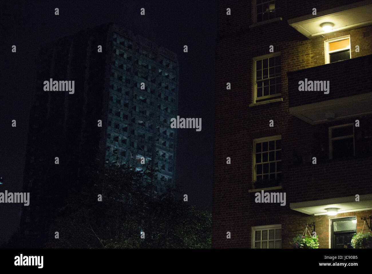 London, UK. 15th June, 2017. Grenfell Tower continues to smoulder, with flames periodically visible, just after - Stock Image