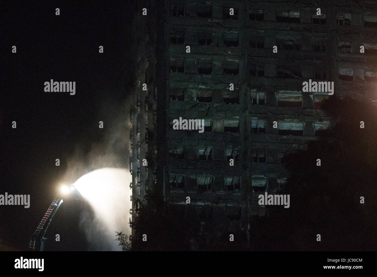 London, UK. 15th June, 2017. Firefighters spray water onto a still smouldering Grenfell Tower at around 1.30am. - Stock Image