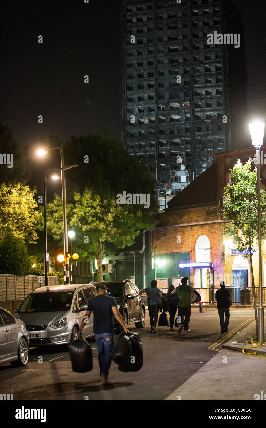 London, UK. 15th June, 2017. People assist with relief efforts by carrying aid parcels close to the Grenfell Tower - Stock Image