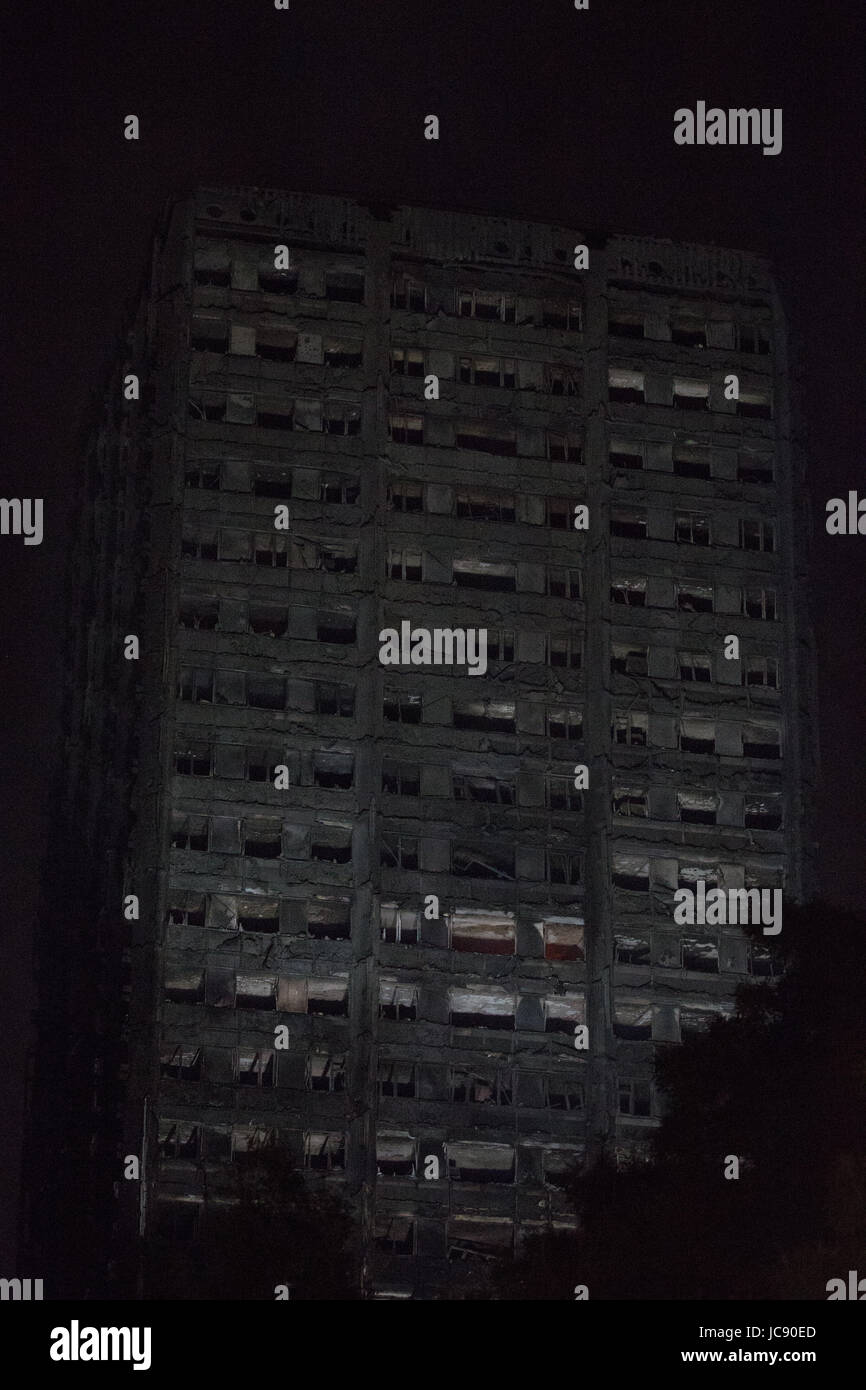 London, UK. 15th June, 2017. Grenfell Tower continues to smoulder, with flames periodically visible, at around 1.30am. - Stock Image