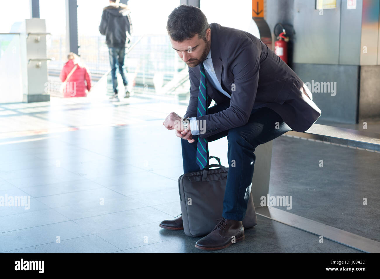 Tired businessman commuter is traveling and is waiting alone - Stock Image