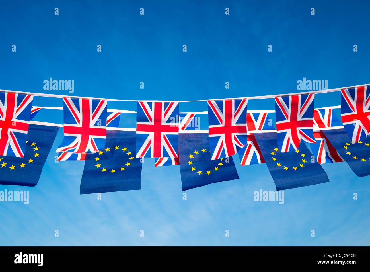 European Union and British Union Jack flag bunting flying in bright blue sky in a statement of the Brexit EU negotiations - Stock Image