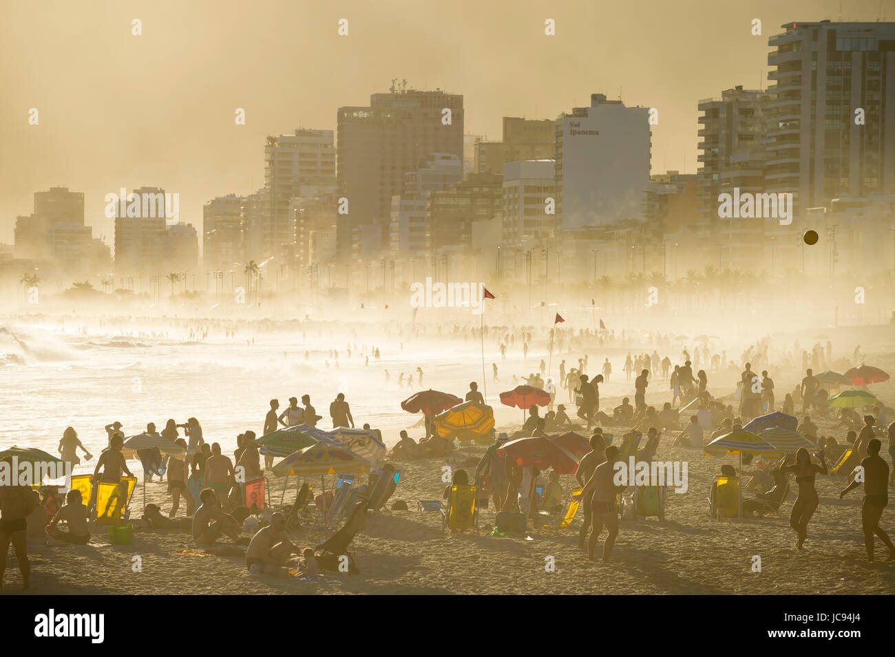 RIO DE JANEIRO - MARCH 20, 2017: Silhouettes of people enjoing the golden misty sunset shores of Ipanema Beach in - Stock Image