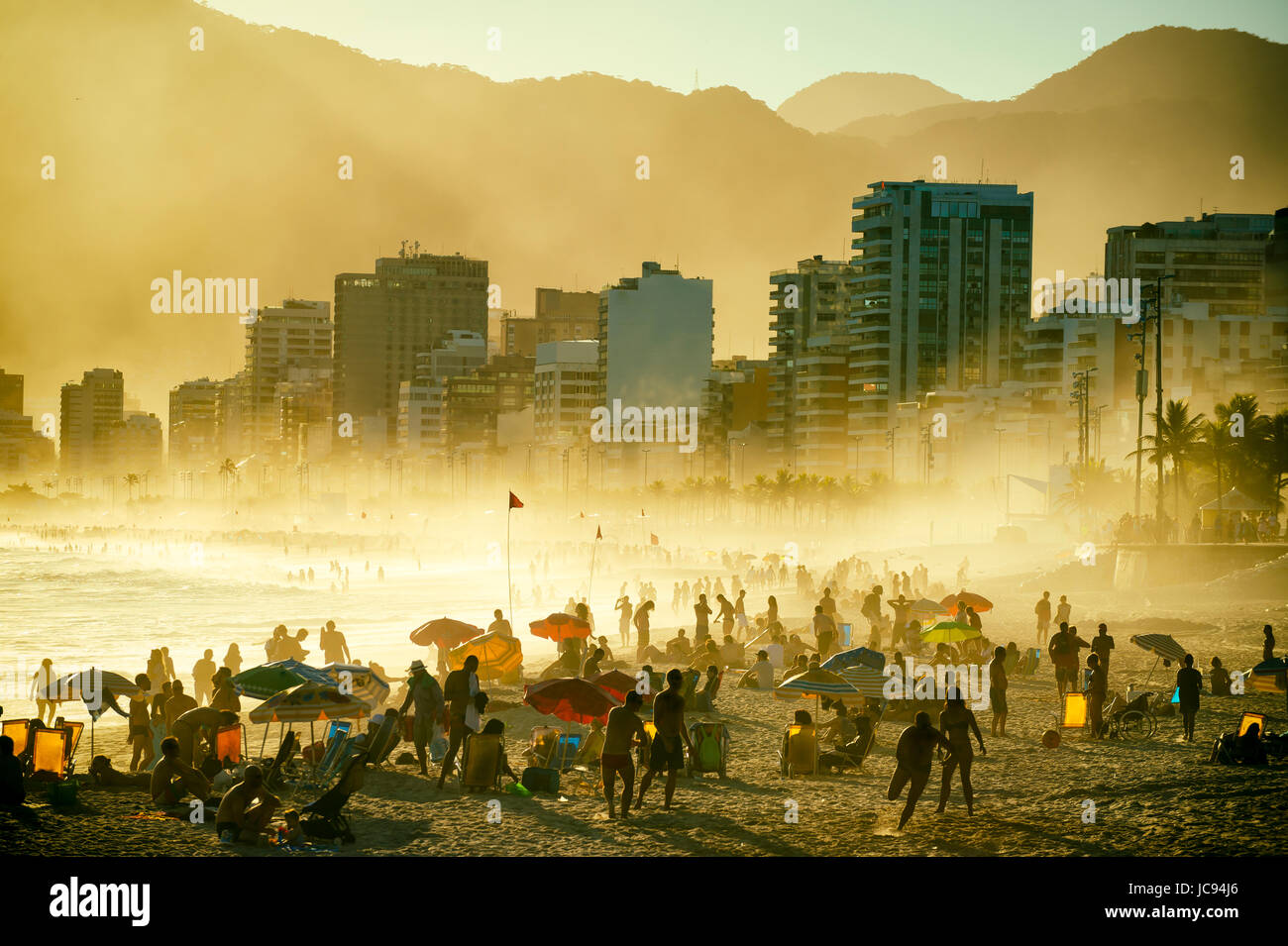RIO DE JANEIRO - MARCH 20, 2017: Silhouettes of people enjoing the golden misty sunset shores of Ipanema Beach in Stock Photo