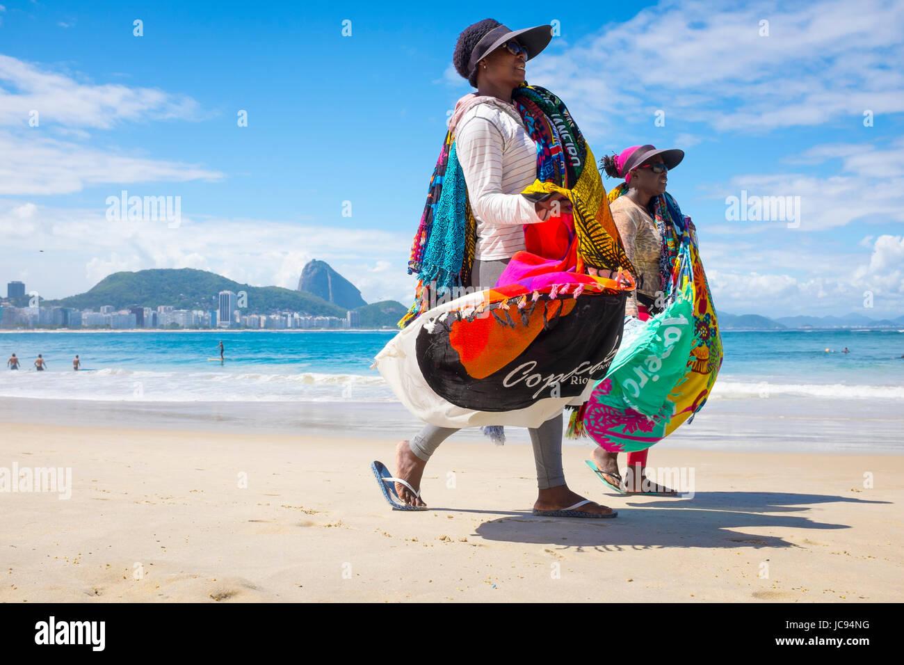 RIO DE JANEIRO - MARCH 21, 2017: Brazilian beach vendors walk along Copacabana Beach selling sarongs or kangas - Stock Image