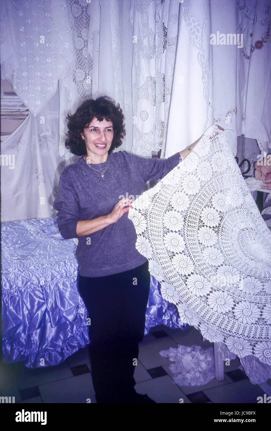 Greek Lady holding and Displaying Hand Made Lace, Kassiopi, Corfu, Greece - Stock Image