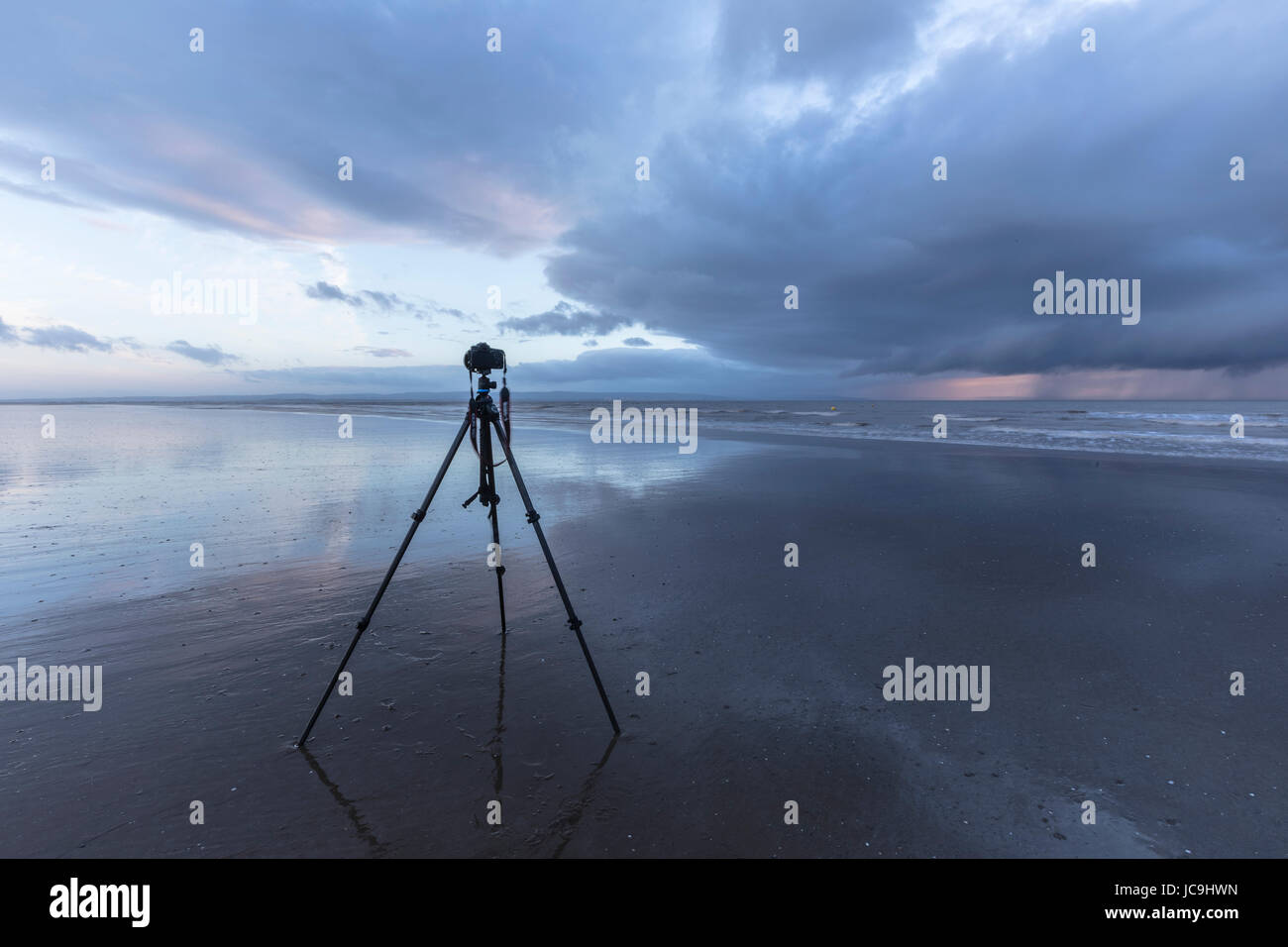 camera on a tripod during low tide at the beach, waiting to capture the sunset - Stock Image